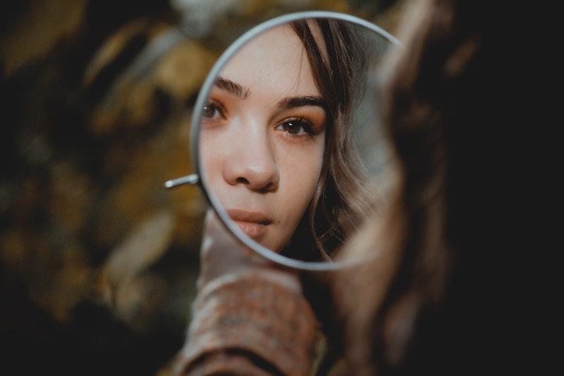 κοπέλα που κοιτάζεται στον καθρέφτη